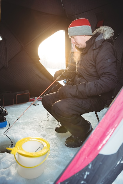 座って釣りをする氷の漁師 無料写真