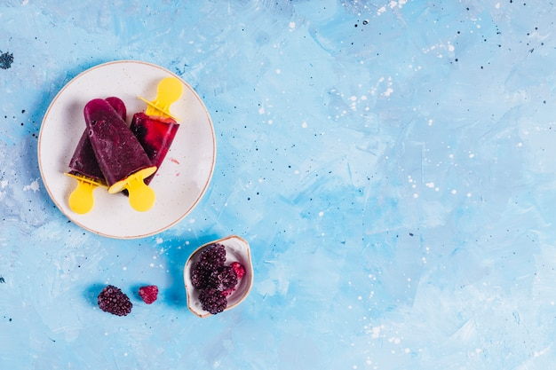 Ice lollies and berries on blue background Premium Photo