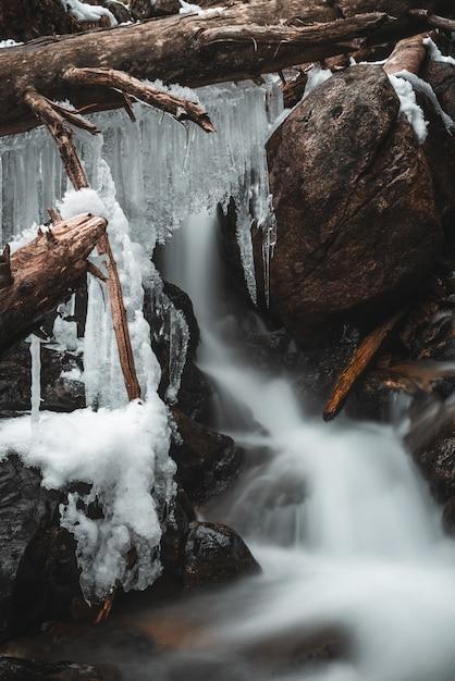 Stalattiti di ghiaccio su tronchi in una cascata Foto Gratuite