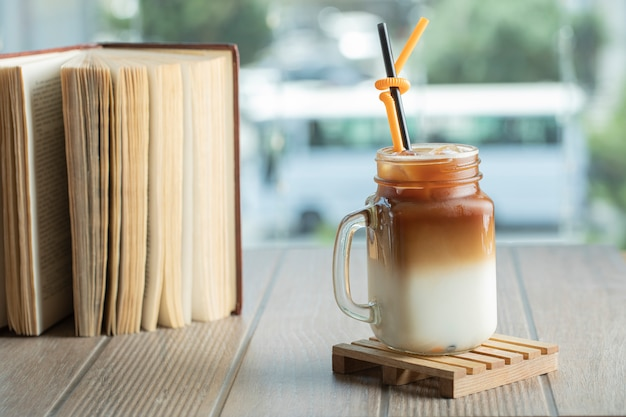 Ice tea with caramel sauce and milk in the jar on the table Free Photo