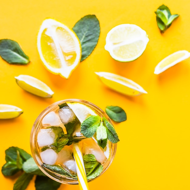Ice tea with ice, lemon and mint on a combined colored yellow background Premium Photo