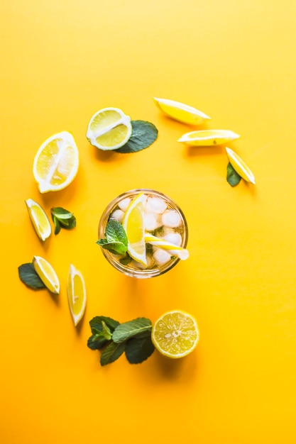 Ice tea with ice, lemon and mint on a combined colored yellow background. Premium Photo