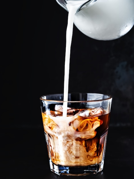 Iced coffee in a glass with ice and sugar syrup Free Photo