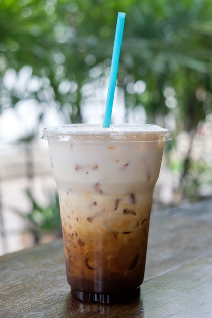 Iced coffee latte in takeaway cup on nature bokeh ...