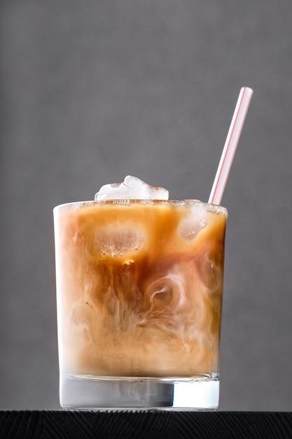 Iced coffee with cream on dark wooden table Premium Photo