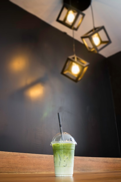 Iced green tea latte on wooden table Premium Photo