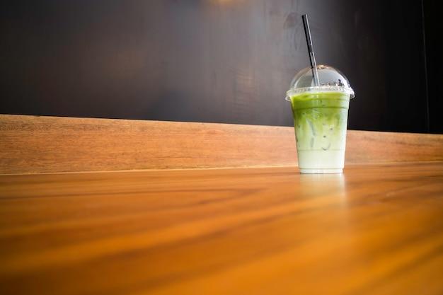 Iced green tea latte on wooden table Premium Photo