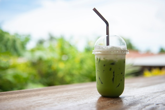 Iced green tea in plastic cup / matcha green tea latte frappe and straw on wooden table with nature Premium Photo