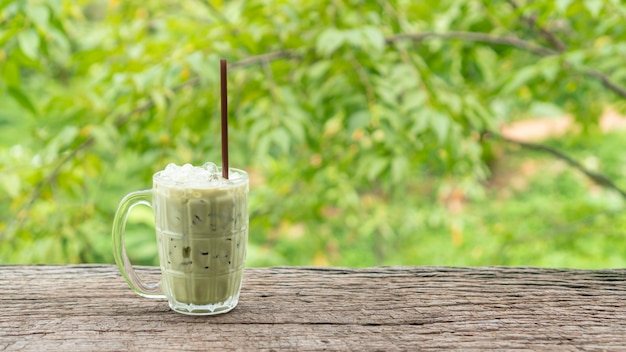 Iced green tea on a wooden table and green nature Premium Photo