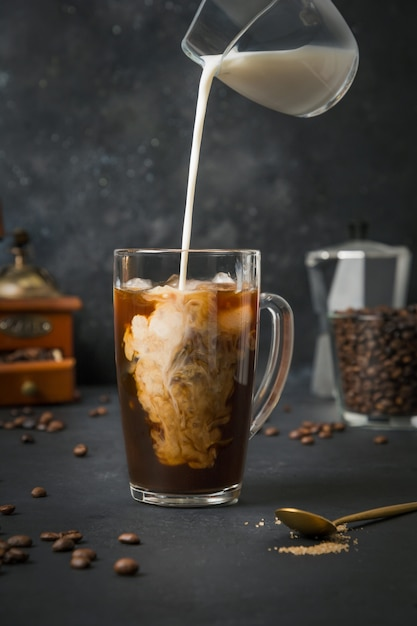 Premium Photo Iced Latte Coffee In Cup Glass With Pouring Milk On Black