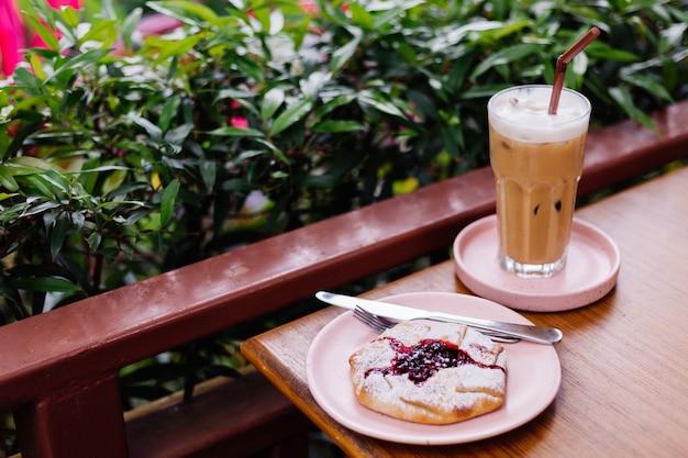 여름 카페 녹색 숲에 나무 테이블과 크랜베리 파이에 분홍색 스탠드에 유리에 아이스 라떼 무료 사진