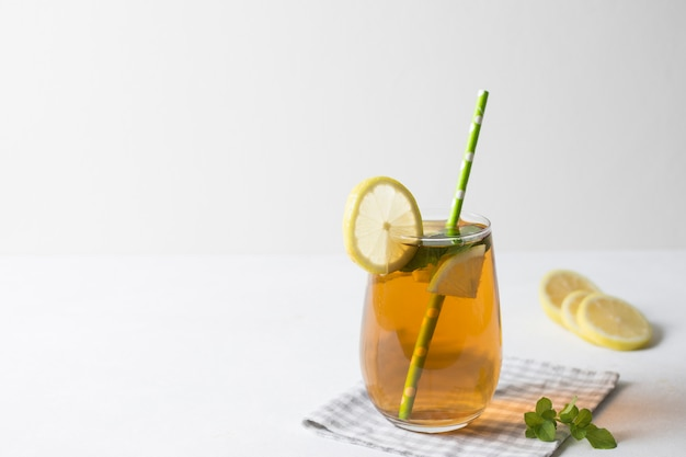 Iced lemon slices and mint leaves herbal tea on tablecloth against white background Premium Photo