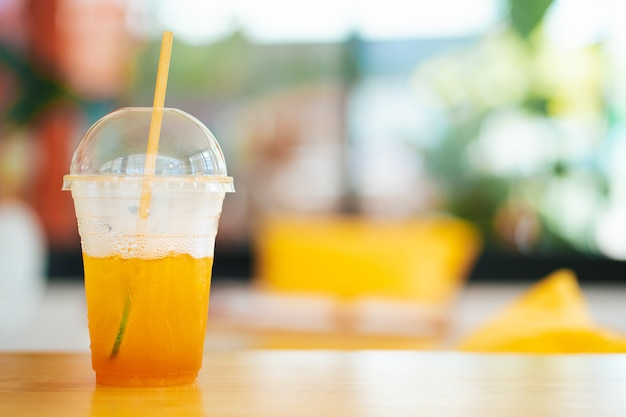 コーヒーショップでプラスチックのマグカップでアイスレモンティー Premium写真