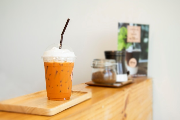 Iced milk tea with straw in plastic cup on counter. Premium Photo