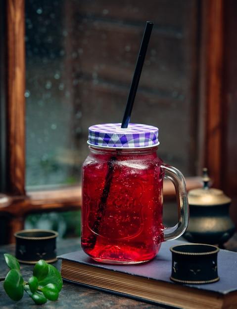 Bevanda rosa ghiacciata in barattolo di vetro con cannuccia nera davanti alla finestra Foto Gratuite