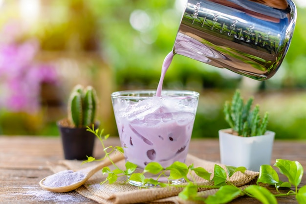 Iced purple taro milk in clear glass served on wooden table in garden cafe Premium Photo
