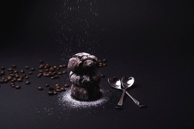 Icing sugar falling on cocoa cookies stacked with roasted coffee beans and spoon on black backdrop Free Photo