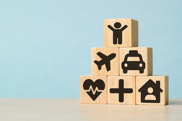 Иконки на деревянных игрушечных блоках сложены в форме пирамиды. понятия физического осмотра для здравоохранения и медицинского страхования. понятие страхования Premium Фотографии