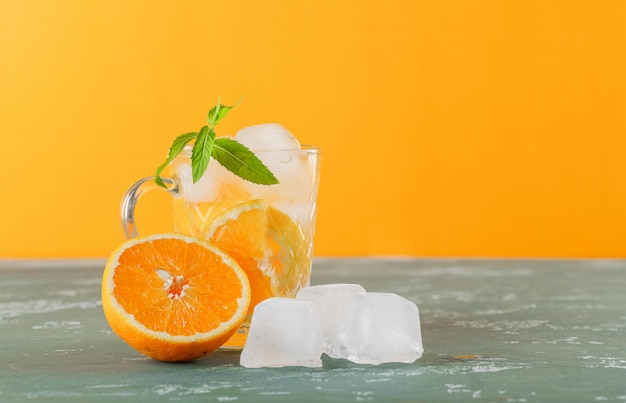 Icy detox water in a cup with orange, mint side view on plaster and yellow background Free Photo