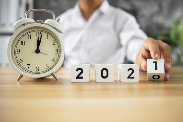 アイデアと事業計画の時間の概念、ビジネスマンは木製のテーブルで2020年から2021年のキューブ番号を回します Premium写真
