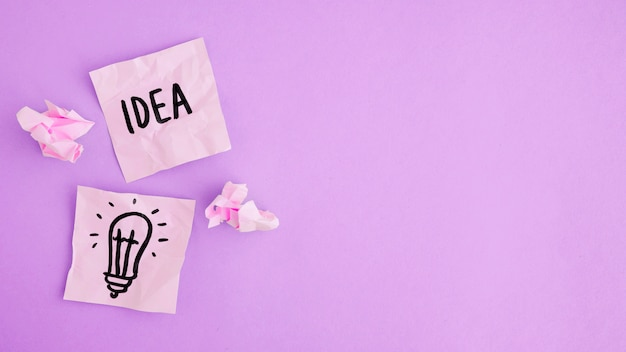 idea and light bulb drawn on two sticky notes with paper ball on