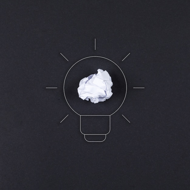 Idea concept with lamp, crushed paper on black background top view. horizontal image Free Photo