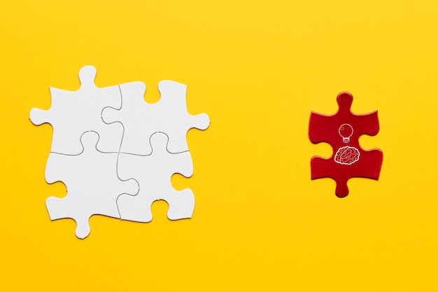 Idea icon on red puzzle piece standing near white joint puzzle piece over yellow backdrop Free Photo