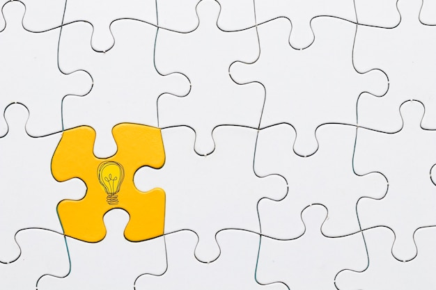 Idea icon on yellow puzzle piece connected with white grid puzzle backdrop Free Photo