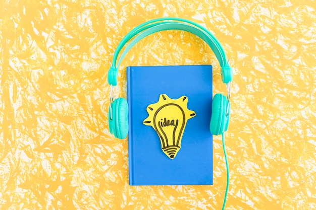 Idea light bulb on blue cover notebook with headphone on yellow backdrop Premium Photo