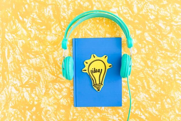 Идеальная лампочка на ноутбуке с голубой крышкой с наушниками на желтом фоне Premium Фотографии