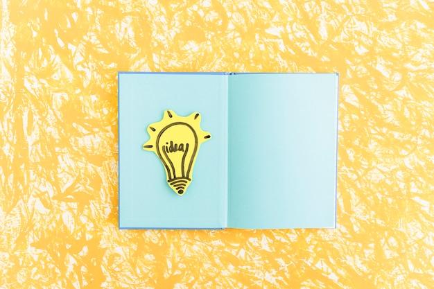 Идеальная лампочка на синем ноутбуке страницы над желтым текстурированным фоном Бесплатные Фотографии