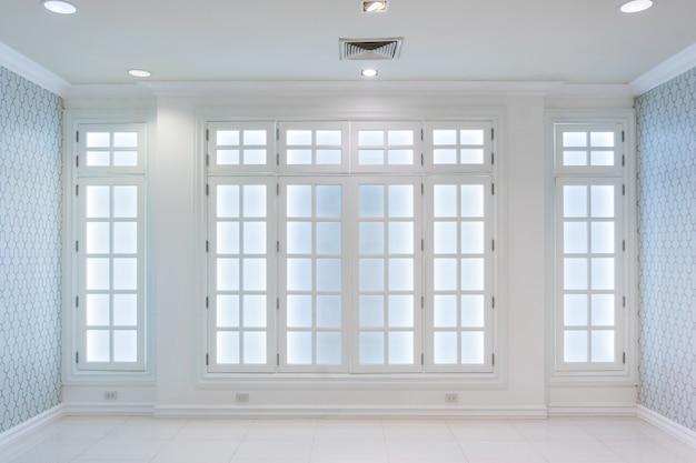 흰색 바닥과 큰 벽과 흰색 풍경 창에서 흰색 빈 스칸디나비아 룸 인테리어의 아이디어. 프리미엄 사진