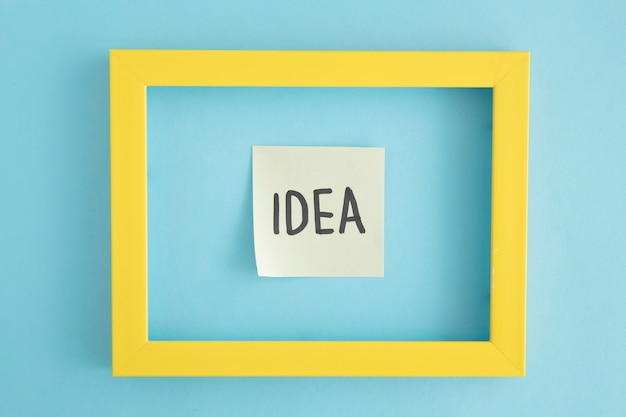 An idea sticky note with yellow border over the blue background Free Photo
