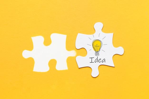 アイデアテキストと黄色の背景上のパズルのピーススタンプとジグソーパズルのピースのアイコン Premium写真