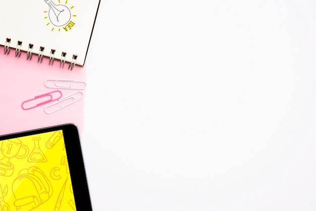 Idea text and hand drawn light bulb on spiral notepad with digital tablet on white background Free Photo
