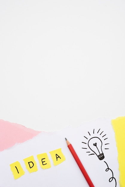 Idea text and hand drawn light bulb with pencil on paper over white backdrop Free Photo