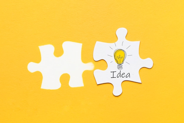 Idea text and icon on jigsaw puzzle piece with puzzle piece stamp over yellow background Free Photo