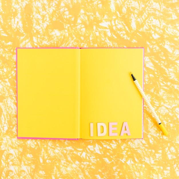 Текст идеи в открытой пустой книге с войлочным наконечником над текстурированным фоном Бесплатные Фотографии