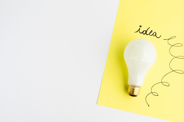 Idea text written on adhesive note with light bulb over white background Free Photo