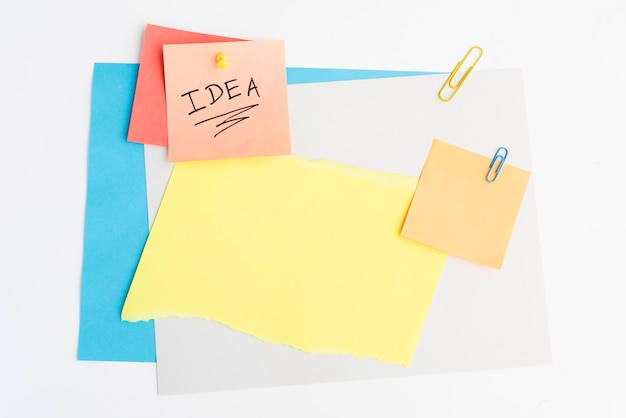 Idea text written on sticky note with pushpin and paperclip on white board Free Photo