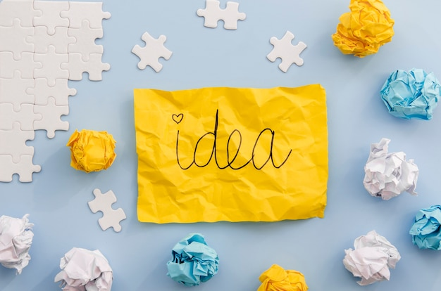 Idea written on a yellow paper with pieces of puzzle Free Photo