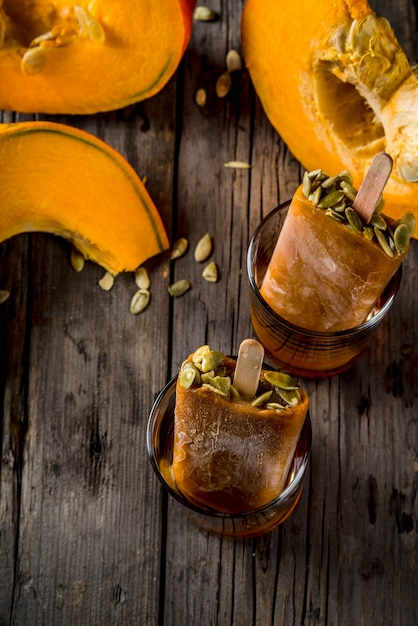 Ideas for autumn dishes from pumpkins. treats for a thanksgiving party, halloween. pumpkin ice cream popsicles with seeds, in glasses with maple syrup. on wooden old rustic table. copy space top view Premium Photo