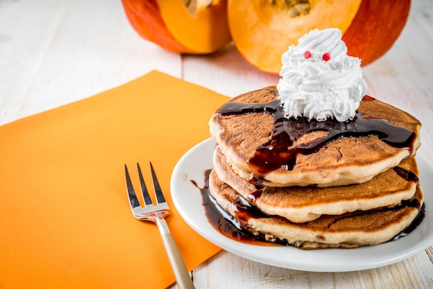 Ideas for children's breakfast, treats for thanksgiving and halloween. pancakes with chocolate sauce and whipped cream in the form of a ghost. on a white wooden table, Premium Photo