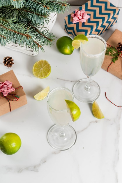 Premium Photo Ideas For Christmas And New Year Drinks Champagne Margarita Cocktails Garnished With Lime And Salt On White Table With Xmas Decorations Copy Space