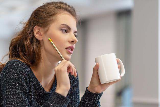 비즈니스를위한 아이디어. 집에서 공부하고 일합니다. 부엌에서 메모장을 사용 하여 메모를 만드는 사려 깊은 젊은 여자. 무료 사진