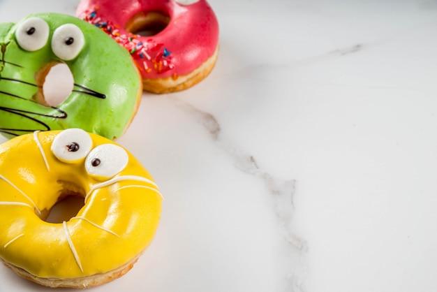 아이들을위한 아이디어는 할로윈을 다룹니다. 눈, 녹색, 노란색, 빨간색 초콜릿 설탕 장식으로 괴물의 형태로 다채로운 도넛. 흰색 대리석 테이블에. 공간 복사 프리미엄 사진
