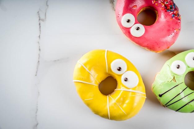 아이들을위한 아이디어는 할로윈을 다룹니다. 괴물의 형태로 화려한 도넛 프리미엄 사진
