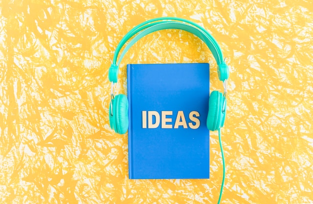 Ideas text on blue cover notebook with headphone on yellow backdrop Premium Photo