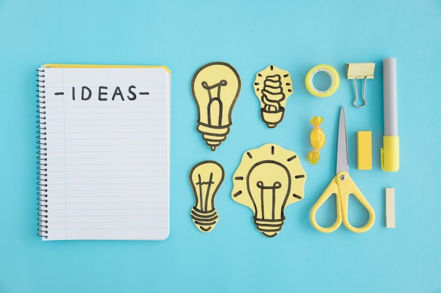 Ideas text on spiral notebook; light bulbs and stationery on blue background Free Photo