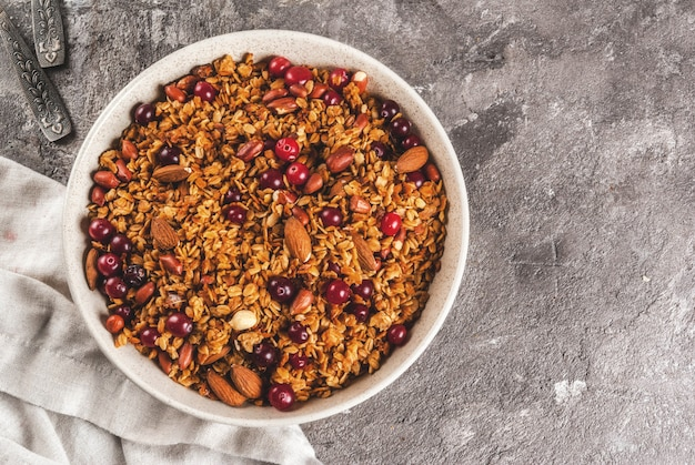 Ideas for a winter, autumn breakfast. thanksgiving, christmas. homemade fresh cooked honey granola with nuts (almonds, peanuts, hazelnuts) and cranberries. on gray concrete table, copyspace top view Premium Photo